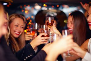 event beautiful women clinking glasses in limousine. focus on glasses
